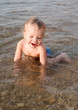 Happy toddler boy playing on the sea