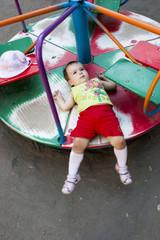 Ребёнок лёжа катается на карусели