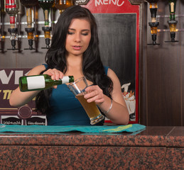 young woman pouring drink in pub