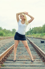 Attractive blond woman posing on railway.