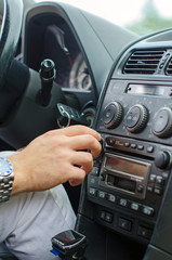 Man's hand tuning radio in the car.