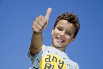 Niño con pelo rizado rubio haciendo gesto de OK