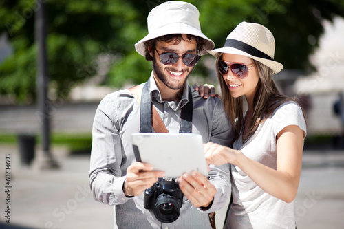 Couple of tourists using a digital tablet