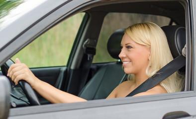 Pretty blond woman driving a car.