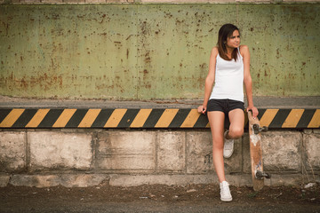 Beautiful skater girl in summer city