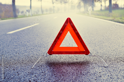 Bad Weather Driving - Warning Triangle on a Misty Road - 68735042