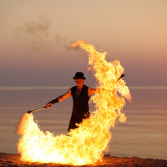 Fire performer with a torch on sunset background
