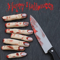 Halloween concept : fingers in blood with knife on a dark backgr