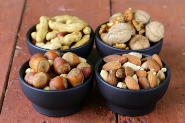 different kinds of nuts in bowls (almonds, hazelnuts, peanuts)