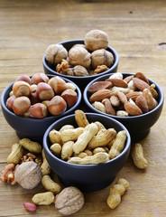 different kinds of nuts in bowls (almonds, walnuts, peanuts)