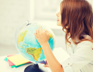 curious student girl with globe at school
