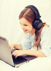 girl with laptop computer and headphones at home