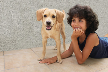 Curly little boy and cute labrador together in a game