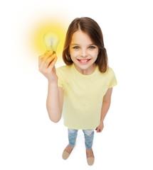 smiling little girl holding light bulb
