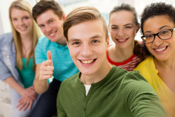 five smiling students taking selfie at school