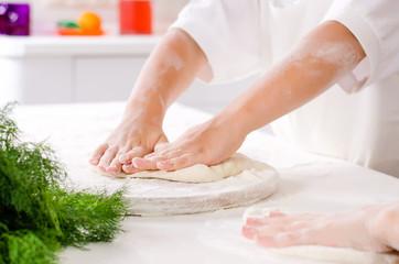Young boy kneading dough