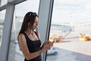 Young woman writing sms on phone while waiting for flight