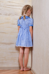 Little girl standing in the corner facing the wall