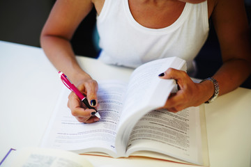 Cropped view of a desktop with open book and hands