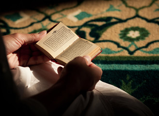 Young woman reading the Quran in the mosque