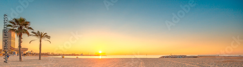 canvas print picture Barceloneta Beach in Barcelona at sunrise