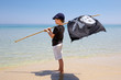 Cute boy dressed as pirate on tropical beach