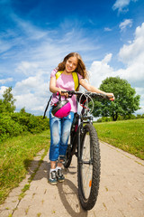 Girl with long hair holds her bike and helmet