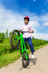 African boy with one wheel of bike up rides it