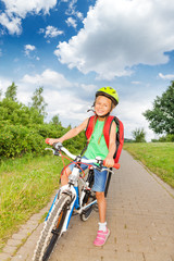 Happy blond girl with braids in bicycle helmet