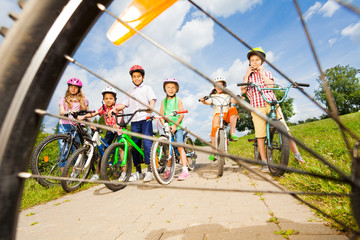 View from bicycle spoke on kids with helmets