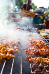 Close-up of chicken pieces grilled on skewers with smoke steel