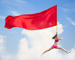 Beautiful Asian female jumping with big red flag