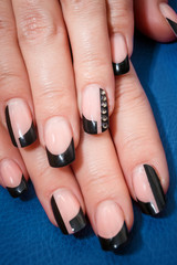 Female hands with black manicure on the blue background