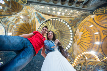 Young couple tourists inside the Blue Mosque on a background of
