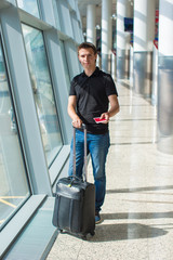Man holding passport and boarding pass at airport waiting the