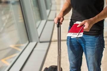 Man holding passports and boarding pass at airport while waiting