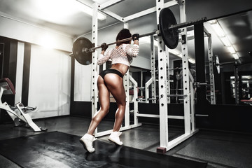 Young sexy girl in the gym doing squat with barbell © Fotokvadrat