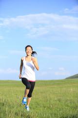 Runner athlete running on sunrise grass seaside
