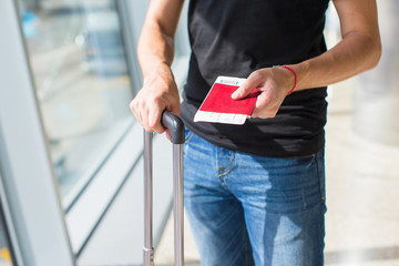 Man holding passports and boarding passport at airport waiting