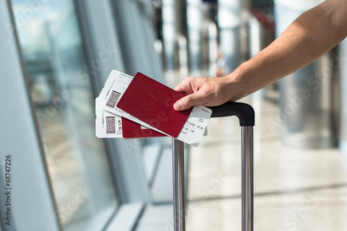 Plexiglas Luchthaven Closeup of man holding passports and boarding pass at airport