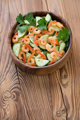 Shrimps, cucumber and lime salad over wooden background