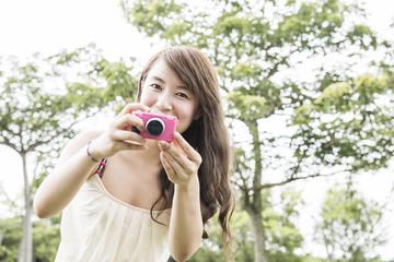 A beautiful Asian girl holding a camera model