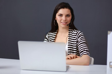 Beautiful business woman working at her desk with headset and l