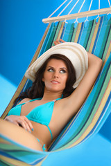 Woman relaxing on hammock with white hat