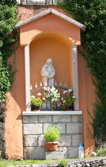 votive capitals with the statue of the madonna in the village