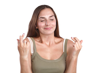 Portrait of woman crossing fingers against white background.