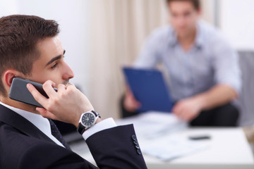 Business people talking on phone at office
