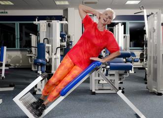 Reife Frau im Fitness Studio an Trainingsgerät Bauch und Rücke