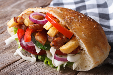 Doner with meat, vegetables and fries in pita bread close-up