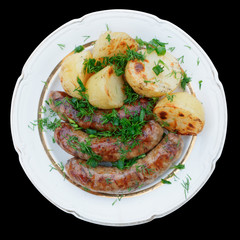 Grilled sausages and potatoes isolated on black